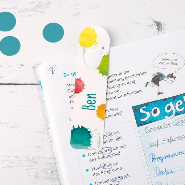 Bunt bedrucktes Lesezeichen mit Farbklecksen und Namensaufdruck