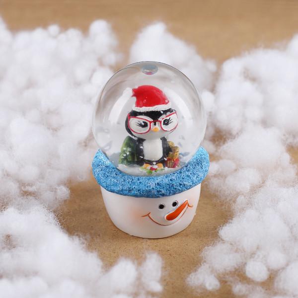 Schneekugel mit Weihnachts-Pinguin auf Schneemann-Sockel