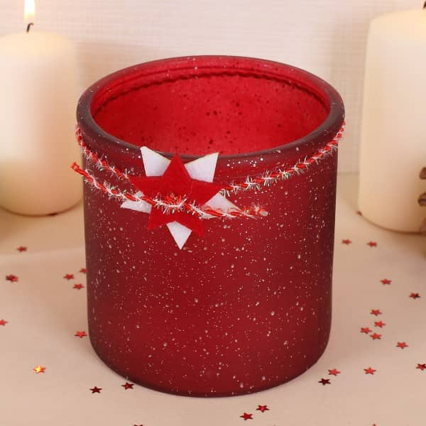 Windlicht aus Glas in rot mit weihnachtlichen Accessoires