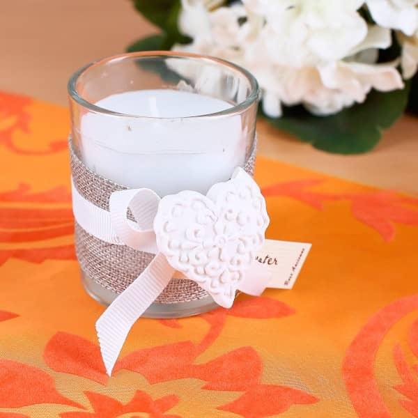 Duftkerze im Glas mit Schleifenband und Herzdeko zur Hochzeit