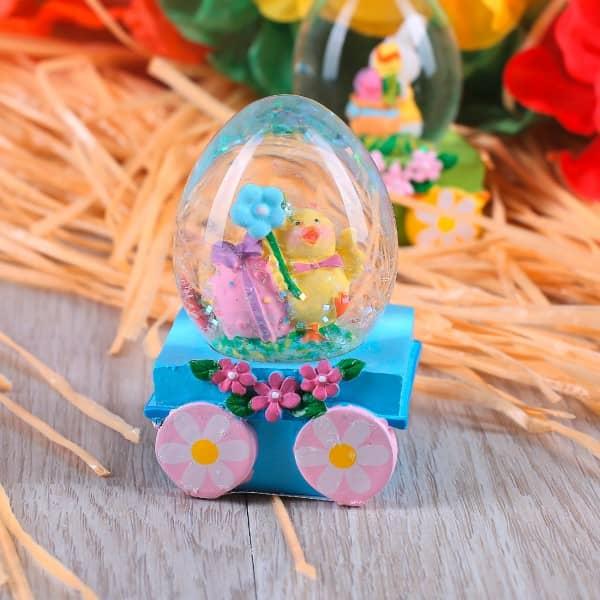 Glitterkugel Osterei auf Wagen mit Blumendeko