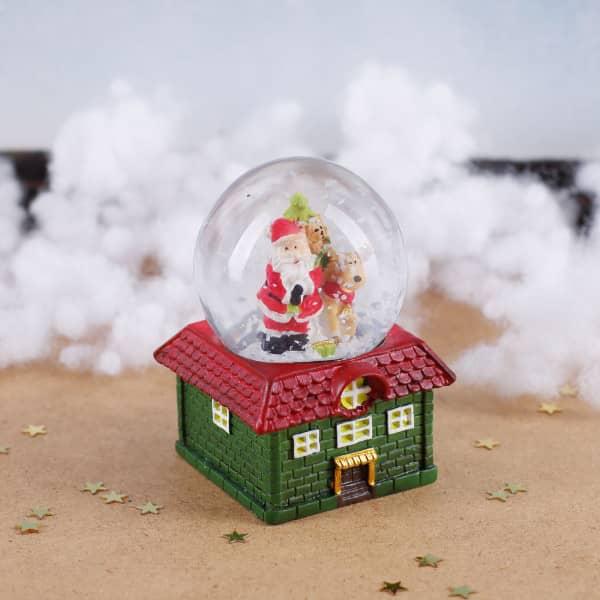 Schneekugel Weihnachtsmann und Rentier auf grünem Haus