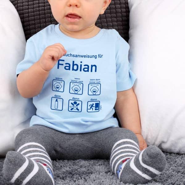 Blaues Babyshirt mit Gebrauchsanweisung