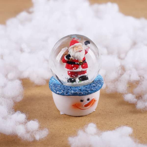 Schneekugel mit Weihnachtsmann auf Schneemann-Sockel