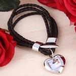 Schwarzes Armband mit Herzanhänger für ein Foto