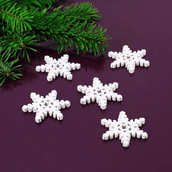 Kleine Schneeflocken aus Holz in weiß