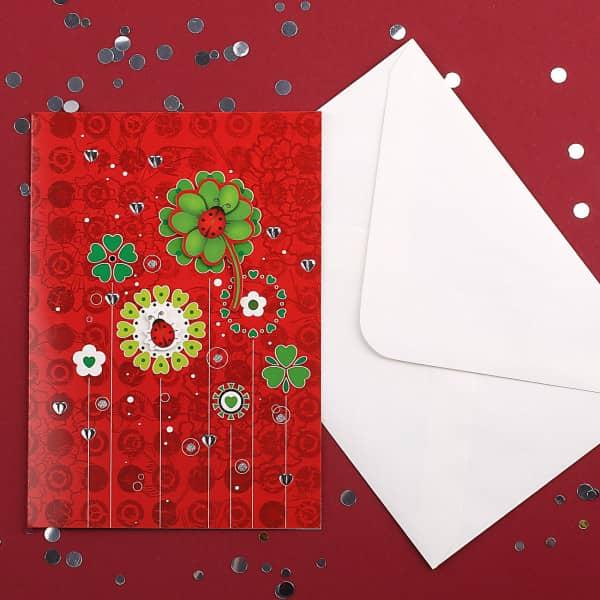 Rote Glückwunschkarte mit Kleeblatt und Marienkäfer