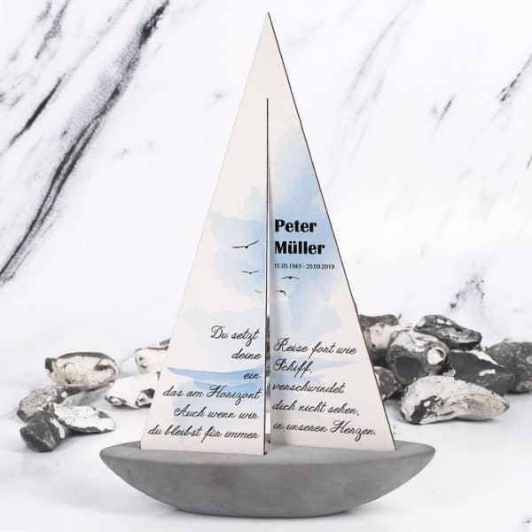 Segelschiff für Verstorbene mit Aufdruck des Namens und des Datums auf dem Segel des Boots