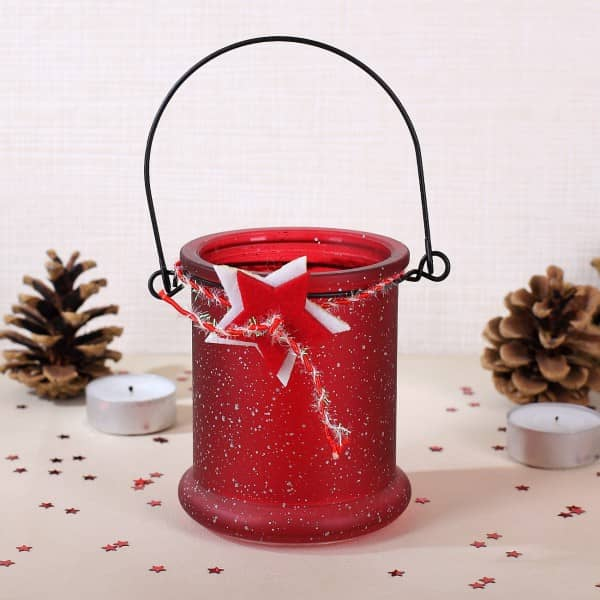 Windlicht zur Weihnachtszeit mit Metallbügel und Sternen in rot