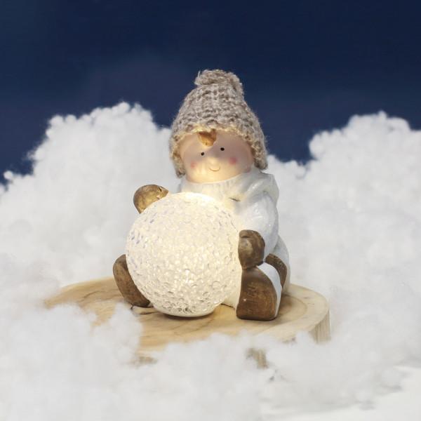 Kleiner Junge mit leuchtender Schneekugel