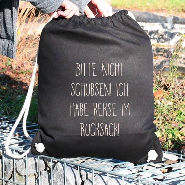 Rucksack in Schwarz mit dem Spruch Bitte nicht schubsen! und Ihrem Wunschtext