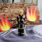 Kleine Feuerwehrmann-Figur mit Schlauch