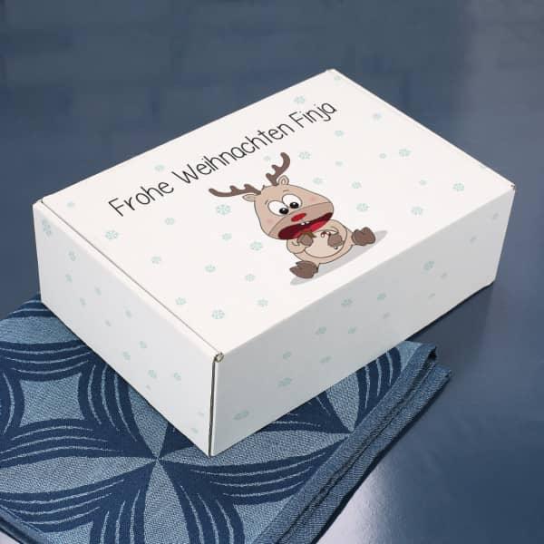 Geschenkverpackung mit niedlichem Rentier und Wunschtext